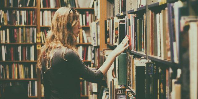 kobieta przeglądająca książki w bibliotece